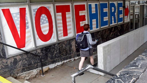 FILE - In this Sept. 23, 2016 file photo, a voter woman passes a large sign before voting in Minneapolis. If Donald Trump or Hillary Clinton scores a high note or commits a blunder in Sunday's presidential debate, millions of voters can respond almost immediately. They can fill out a mail-in ballot right away, or head to a polling location the next day. (AP Photo/Jim Mone, File)