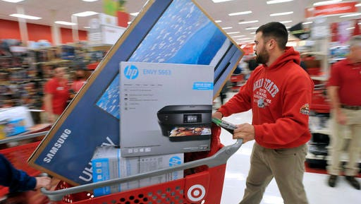 A man pushes his cart filled with appliances in the Target store in Plainville, Mass., shortly after the store opened at 1 a.m. Friday, Nov. 25, 2016. Large screen televisions and small electronics were among the popular items purchased. Stores open their doors Friday for what is still one of the busiest days of the year, even as the start of the holiday season edges ever earlier.