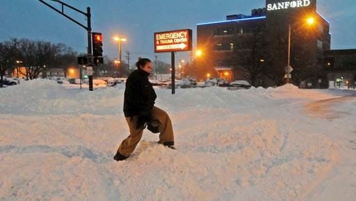 Madori Griffin, who said her car was snowed in, climbs over a snowbank to get to Sanford Hospital early Monday, Dec. 26, 2016, in Bismarck, N.D. The combination of freezing rain, snow and high winds that forced the shutdown Sunday of vast stretches of highways in the Dakotas continued into Monday morning, and authorities issued no-travel warnings for much of North Dakota. (Tom Stromme/The Bismarck Tribune via AP)