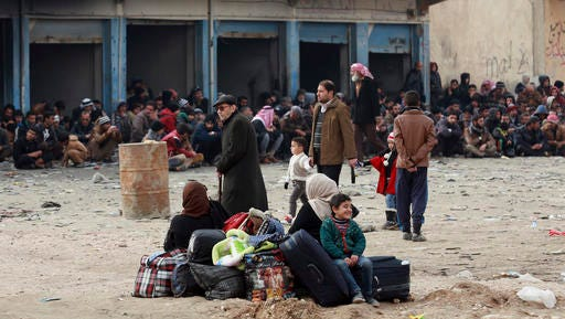 Displaced Iraqis, who fled fighting between Iraqi security forces and Islamic State militants, waiting at the gathering point to be taken for a camp for internally displaced people, in Bartella, around 19 miles (kilometers), from Mosul, Iraq, Saturday, Dec 31, 2016.