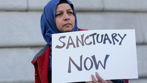 """Moina Shaiq holds a sign at a rally outside of City Hall in San Francisco, Wednesday, Jan. 25, 2017. President Donald Trump moved aggressively to tighten the nation's immigration controls Wednesday, signing executive actions to jumpstart construction of his promised U.S.-Mexico border wall and cut federal grants for immigrant-protecting """"sanctuary cities."""""""