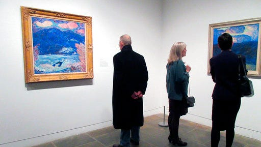 """This March 20, 2017 photo shows visitors looking at paintings from the """"Marsden Hartley's Maine"""" show at The Met Breuer Museum in New York. Hartley was a native of Maine and the exhibition showcases his landscapes and portraits of Maine. Maine's tourism agency has created itineraries that match the artwork for travelers who'd like to visit the places depicted in the paintings."""