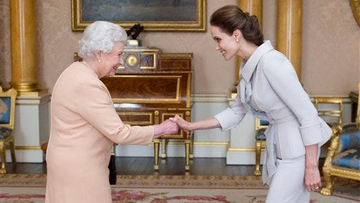 U.S actress Angelina Jolie, right, is presented with the Insignia of an Honorary Dame Grand Cross of the Most Distinguished Order of St Michael and St George by Britain's Queen Elizabeth II at Buckingham Palace, London, Friday.  Jolie received an honorary damehood (DCMG) for services to UK foreign policy and the campaign to end war zone sexual violence.