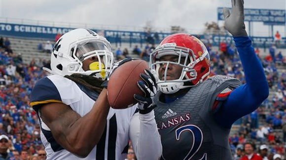 West Virginia wide receiver Kevin White (11) makes a touchdown catch while covered by Kansas cornerback Dexter McDonald (12) during the second half of an NCAA college football game at Kansas Memorial Stadium in Lawrence, Kan., Saturday, Nov. 16, 2013. Kansas defeated West Virginia 31-19. (AP Photo/Orlin Wagner)