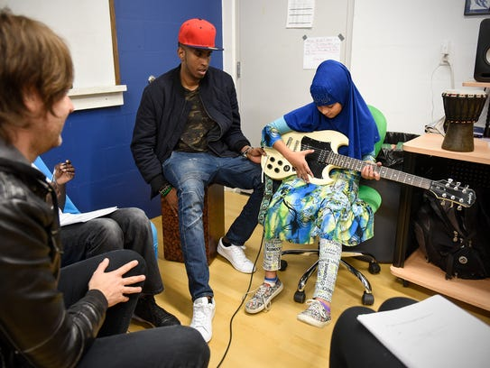 Waayaha Cusub hip hop group musicians work with children