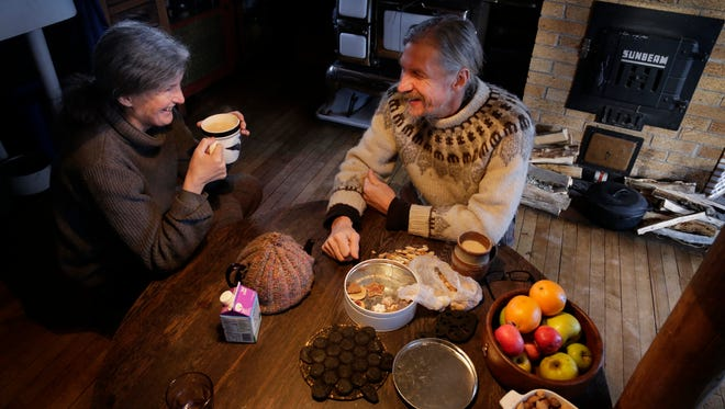 Victoria and John Jungwirth drink tea and finish a tin of cookies in their cabin in Michigan's Upper Peninsula.