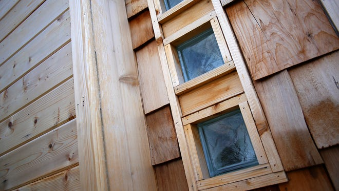 The cedar siding and windows for the shower can be seen from the outside of the tiny house.