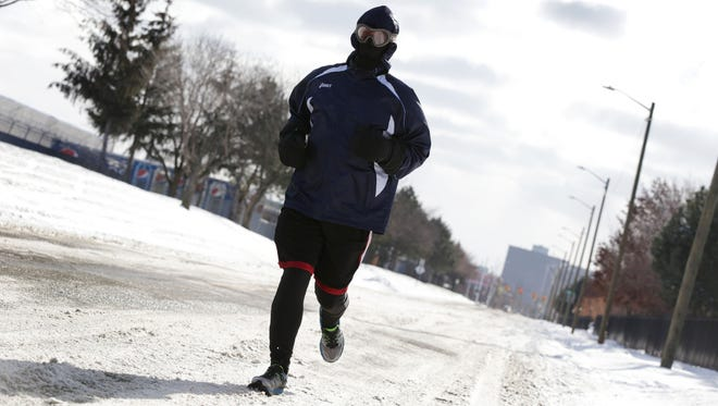 Mikel Smith, 60, who runs about 5 times a week, does a 15 mile run through Eastern Market in Detroit on January 1, 2018. Smith says to make sure that you are layered up if running in the cold.