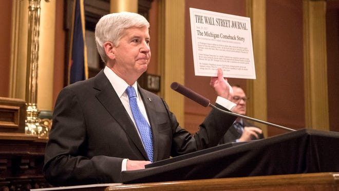 """Governor Rick Snyder delivers his State of the State at the Capitol in Lansing on Tuesday, January 23, 2018. He is holding a Wall Street Journal article touting """"The Michigan Comeback Story."""""""