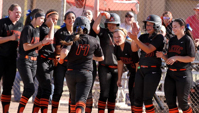 The Aztec Lady Tigers welcome Paige Adair at home plate after her home run against Farmington on March 19 at the Ricketts Park softball fields in Farmington.
