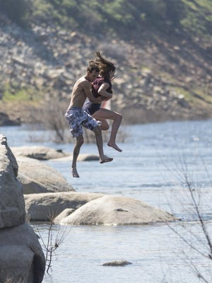 "Micheal Case and Rhiannon Conrad of Visalia leap from a rock into the Kaweah River near Slick Rock on Tuesday, March 14, 2017. He said the water was a ""little chilly."""
