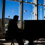FILE PHOTO: Eleazar Misheal Perez Cabrera, a Guatemalan man who is being held in sanctuary at the Shadow Rock Church of Christ in Phoenix, is silhouetted against the church windows as he plays piano on Nov. 26, 2014. The church is once again prepared to offer sanctuary to immigrants who face deportation.
