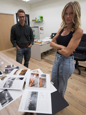 The Armored Frog owners Joe and Alicia Sinkovich review samples of the company's furniture catalog on Monday, Aug. 28, 2017. The Pensacola-based company produces custom-built wood furniture.