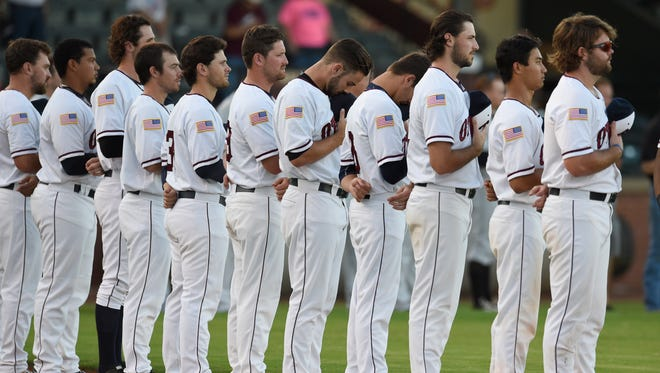 Evansville Otters players remove their caps before going up against the Joliet Slammers in game one of the Frontier League Divisional series at Bosse Field in Evansville Tuesday.