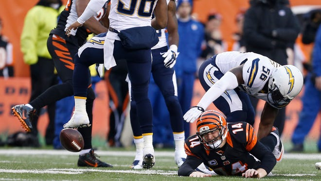 Cincinnati Bengals quarterback Andy Dalton (14) fumbles the ball in the third quarter against the San Diego Chargers in their AFC wild-card playoff game at Paul Brown Stadium. The Enquirer/Jeff Swinger