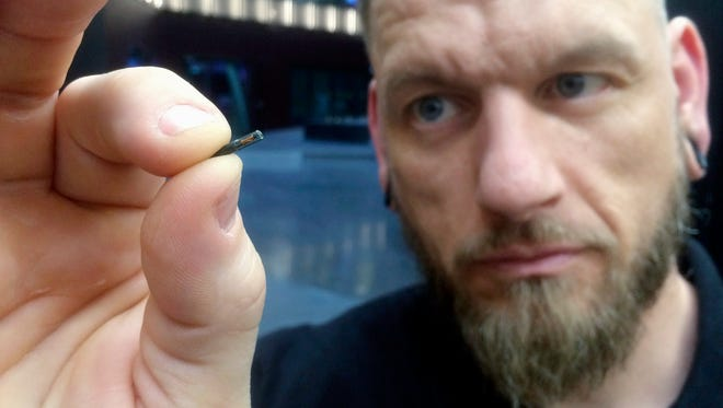 Jowan Osterlund from Biohax Sweden, holds a small microchip implant, similar to those implanted into workers at the Epicenter digital innovation business center