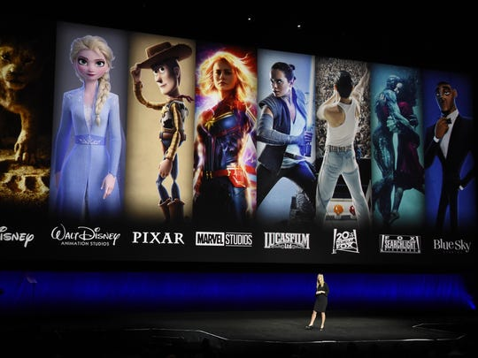 FILE - In this April 3, 2019, file photo characters from Disney and Fox movies are displayed behind Cathleen Taff, president of distribution, franchise management, business and audience insight for Walt Disney Studios during the Walt Disney Studios Motion Pictures presentation at CinemaCon 2019, the official convention of the National Association of Theatre Owners (NATO) at Caesars Palace in Las Vegas. Verizon is offering new and current customers a free year of Disney+ as the battle for streaming customers heats up. The offer extends to certain new and existing 4G and 5G customers as well as new Verizon Fios and 5G home internet customers. The promotion begins Nov. 12. (Photo by Chris Pizzello/Invision/AP, File)