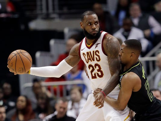Cleveland Cavaliers forward LeBron James (23) works against Atlanta Hawks guard Isaiah Taylor (22) during the first half of an NBA basketball game Friday, Feb. 9, 2018, in Atlanta. (AP Photo/John Bazemore)