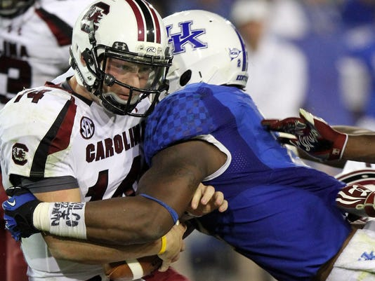 FILE - In this Sept. 29, 2012, file photo, South Carolina's Connor Shaw, left, is sacked by Kentucky's Alvin Dupree during the fourth quarter of an NCAA college football game in Lexington, Ky. Dupree and Za'Darius Smith are back for their senior seasons, good news for Kentucky in many ways. (AP Photo/James Crisp, File)