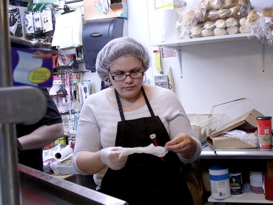 Melody Flores puts on latex gloves before starting work  behind the food counter at her second job at a corner store in the city.