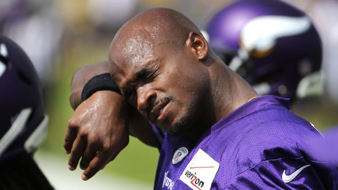"""Minnesota Vikings running back Adrian Peterson wipes the sweat from his face during training camp on July 27, 2015, in Mankato. """"I'm excited as far as what we have and the vision that we have for this season,"""" Peterson said."""