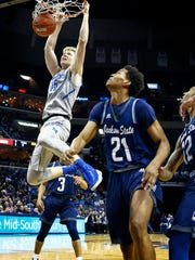 University of Memphis forward Chad Rykhoek (left) dunks in front of  Jackson State University defenders Demetrice Clopton (middle) and Maurice Rivers (right)  during first-half action at FedExForum.