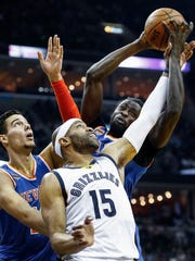 Memphis Grizzlies forward Vince Carter (middle) loses a rebound to New York Knicks defenders Willy Hernangomez (left) and Maurice Ndour (right) during the second quarter at  FedExForum.