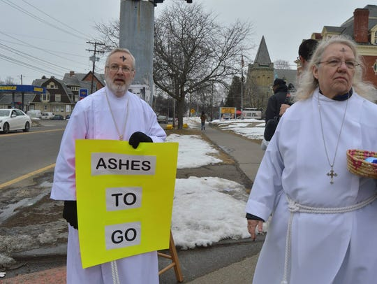 Dave Banner and Judy Mica-Guerin distribute ashes Wednesday