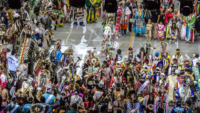 In this April 25, 2015 photo, Native American and indigenous dancers surround head man dancer, Juaquin Hamilton, from Shawnee, Okla., following the grand entrance of the 32nd annual Gathering of Nations in Albuquerque N.M. More than 100,000 spectators, artists, and performers will be converging on Albuquerque as part of North America's largest powwow. The 33rd edition of the three-day festivities get underway Friday, April 29, 2016, at the University of New Mexico basketball arena.
