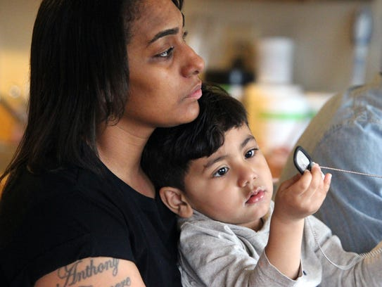 Staff Sgt. Nancy Omundsen holds her son, Alexander, 2, as he plays with her Army dogtags at their Nanuet home. Nancy's husband, Eric, had his car impounded because of toll violations while he was on his way to pick up his wife after a tour of duty in Kuwait and Iraq.