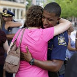 Louisiana state officers and civilians hug in Baton Rouge.