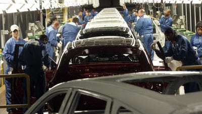 Employees tend to Pathfinder SUVs moving through the Nissan paint plant in Smyrna.