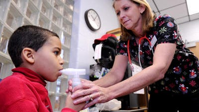 Metro Nashville Health Department Bill Paul wants Metro to fund a nurse in every Metro school. In this photo from 2012, Amy Fisher, nursing coordinator for the Franklin Special School District, helps third-grader Ian Pearson with a breathing treatment at Johnson Elementary.