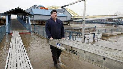 In this 2010 photo, Chris Trahan, general manager of the barge complex that houses the Beer Sellar and Hooters on the Newport riverfront, carries a section of aluminum walkway to provide access to the facility as the Ohio River water rises.