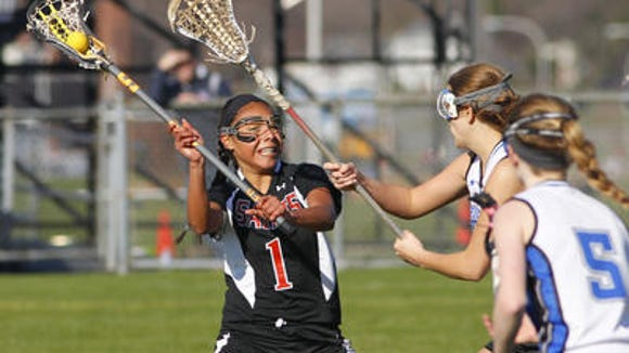 Churchville-Chili's Cheyenne Clark, left, gets a shot off against Brockport's Kirsten Craig, center, and Tori Penders during girls lacrosse action between Brockport Blue Devils and Churchville-Chili Saints in Brockport in April.