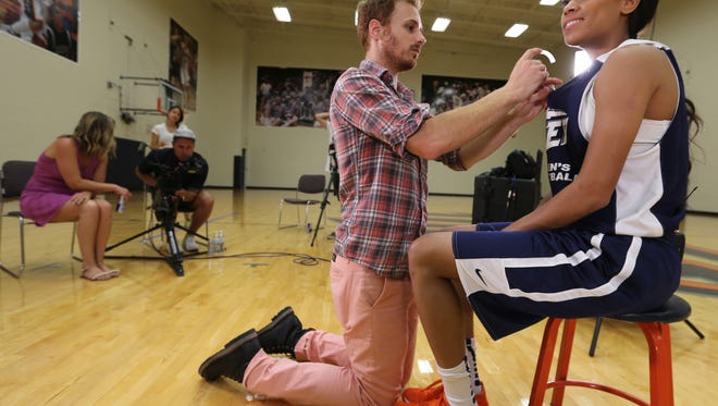 Blake Henderson places a microphone on Cameasha Turner on Thursday in preparation for an interview.