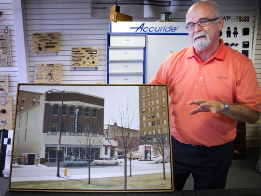 Bob Kurtz holds a painting of his family's old store