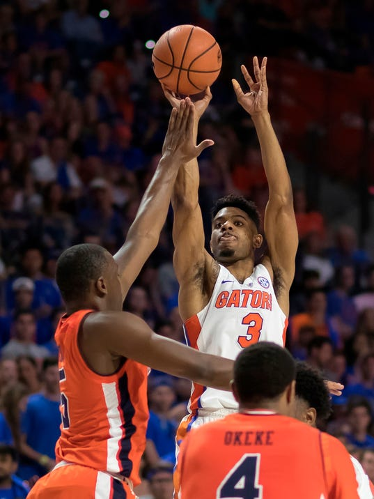 FILE - In this Feb. 24, 2018, file photo, Florida guard Jalen Hudson (3) shoots over Auburn guard Mustapha Heron (5) during the first half of an NCAA college basketball game in Gainesville, Fla. Florida coach Mike White has a rebuilding project ahead, and he's not even quite sure how significant an undertaking it will be. White is waiting to see what happens with leading scorer Jalen Hudson, who declared for the NBA draft late last month but left open the possibility of returning to school for his senior season. (AP Photo/Ron Irby, File)