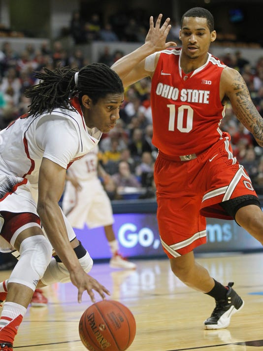 Nebraska forward Terran Petteway tries to control the ball as Ohio State forward LaQuinton Ross (10) defends during the second half of an NCAA college basketball game in the quarterfinals of the Big Ten Conference tournament Friday, March 14, 2014, in Indianapolis. Ohio State won 71-67. (AP Photo/Kiichiro Sato)