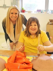 Allison Foster, chairman of the Holy Angels Champions for Individuals with Disabilities Advisory Committee, helps Holy Angels resident Lisa S. with a project.