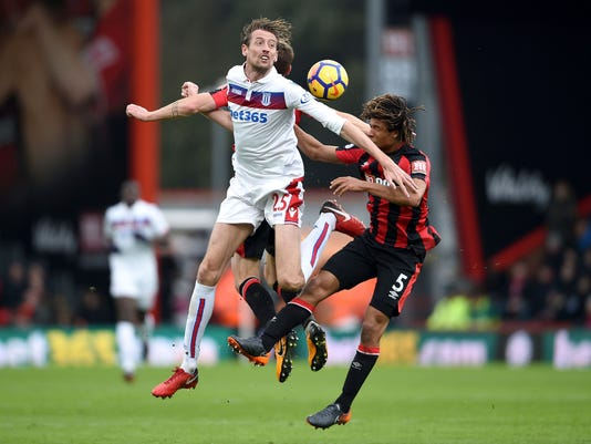 Stoke City's Peter Crouch battles for the ball with Bournemouth's Nathan Ake, right and Dan Gosling, background,  during the English Premier League soccer match between Bournemouth and Stoke City,  at the Vitality Stadium, in Bournemouth, England, Saturday, Feb. 3, 2018. (Daniel Hambury/PA via AP)