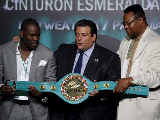 Light heavyweight champion Stevenson, World Boxing Council President Sulaiman and former heavyweight boxing champ Holmes present the Mexican-made title belt in Mexico City