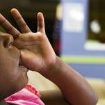 A child sucks her thumb at the Child Crisis Center in Mesa, Ariz.