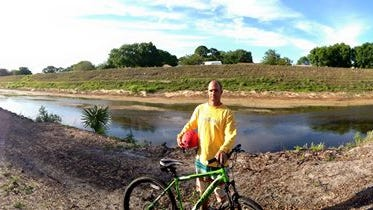 Steven Brigman, 39, a mountain biker from Cocoa Beach, stands beside the Tillman Canal in Palm Bay after riding the Grapefruit Trails.