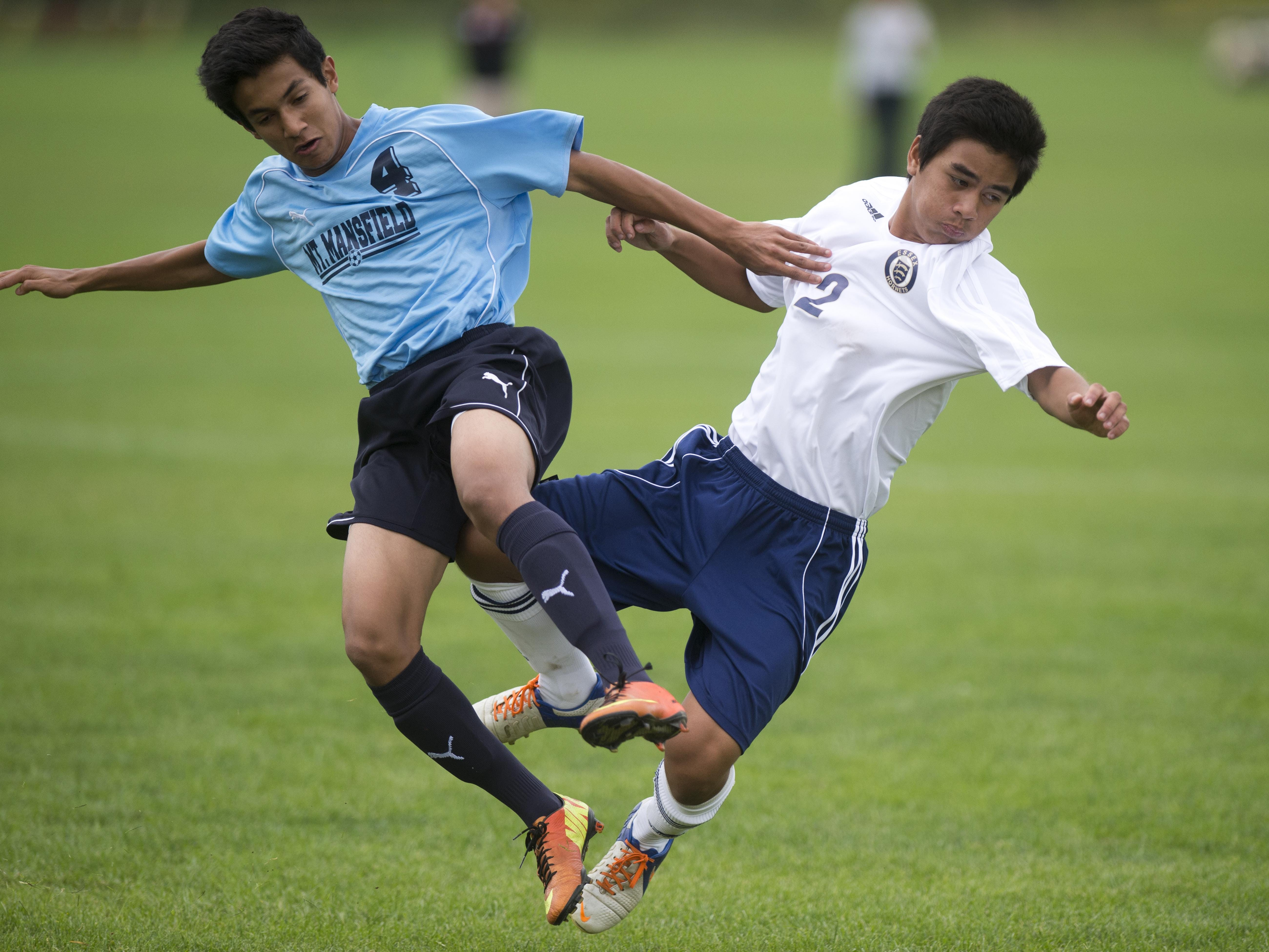 From left, MMU's #4 Kieran Bhave and Essex #2 Hunter Pelkey bounce off each other are fighting for the ball during Tuesday's soccer match at Essex High School.