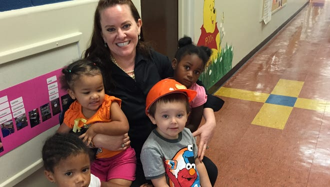 Laura Jane Howald poses outside her classroom with some of her preschool students. Howald was recently named Asheville City Schools Teacher of the Year.