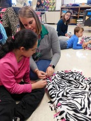 Fifth-grader Belleza Eastburn works with llife-skills teacher Tifanny Purcell on a blanket that will be donated to children in the Ronald McDonald House at Hershey, on Friday, Nov. 17, 2017.