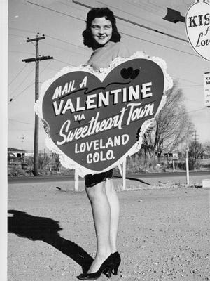 A woman poses with a giant heart on Valentines Day 1962 in Loveland, Colorado.