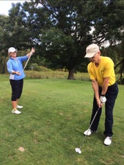 Jorie Ftorek, left, instructing David Oliver on a proper golf swing at Endwell Greens Golf Club.