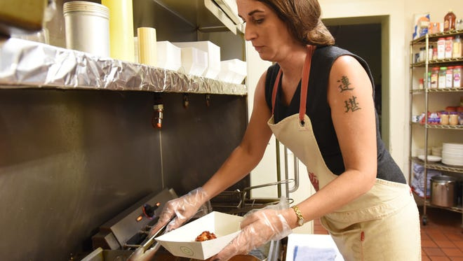 Manager Misty Dillon dips wings at the Rusty Rooster in Duncan Falls.